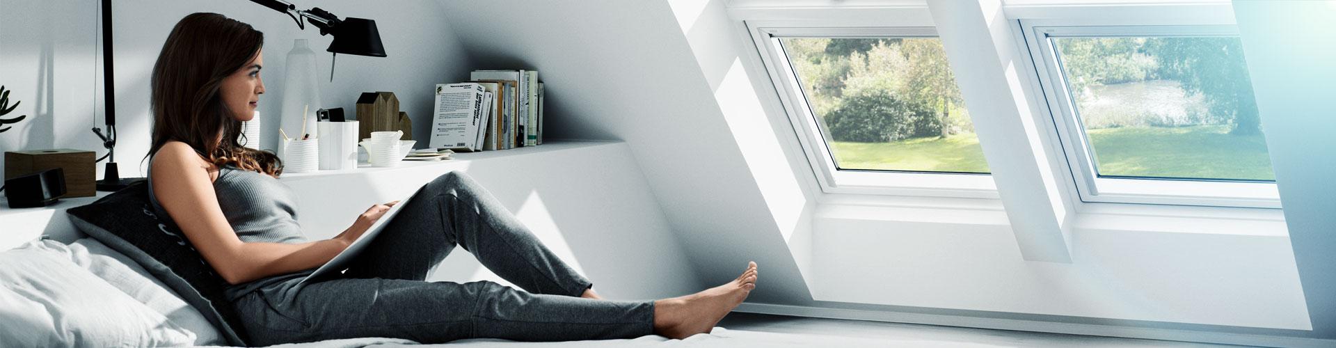 Frau liegt im Bett und blickt aus Dachliegefenster - windooro.de
